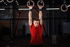 Athlete working out his muscles on rings Royalty Free Stock Photography