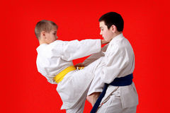 An athlete with a yellow belt beat kneeing athlete with a blue belt Royalty Free Stock Image