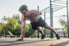 Athlete young man doing one-arm push-up exercise working out his upper body muscles outside in summer. Royalty Free Stock Image