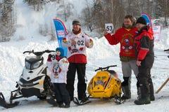 Athleten auf einem Schneemobil fahrung empfingen ihre beginnenden Zahlen lizenzfreie stockfotografie
