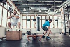 Athleten in der Turnhalle Hocken drücken Ups und Staffellauf stockbilder
