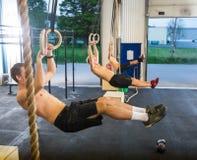 Athleten, die auf gymnastischen Ringen im Kasten baumeln stockfoto