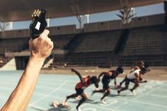 Athleten, die ein Rennen in einem Leichtathletikstadion laufen lassen stockfoto