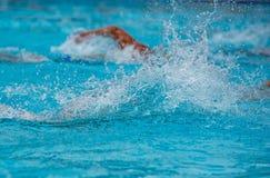 Athleten, die Freistil auf einem Swimmingpool schwimmen stockbilder