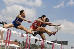 Athleten, die Hürden im Rennen klären stockfotos