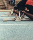 Athleten, die ihre Füße auf Startblöcken auf Laufbahn stillstehen stockfotografie