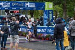 Athleten, die Kreuzungsziellinie im Straßenmarathon gewinnen lizenzfreies stockbild