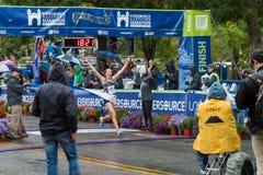 Athleten, die Kreuzungsziellinie im Straßenmarathon gewinnen stockfoto