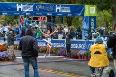 Athleten, die Kreuzungsziellinie im Straßenmarathon gewinnen stockfotos