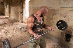 Athleten-Exercising Biceps In-Ruinen stockbilder