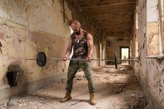 Athleten-Exercising Biceps In-Ruinen stockfoto