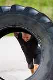 Athleten-Lifting Large Tractor-Reifen auf Straße Stockbilder