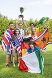 Athleten mit verschiedenen Staatsflaggen feiernd im Park Stockfotografie