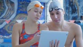 Athleten-Schwimmer, die ein Digital-Tablet verwenden stock footage