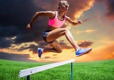 Athletenfrau, die über Hürde gegen bewölkten Sonnenuntergang springt stockfotografie
