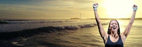 Athletenfrau, die gegen Wellen und Sonnenuntergang feiert lizenzfreie stockbilder
