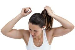 Athletenfrau, die ihr Haar bindet und Musik hört lizenzfreies stockbild