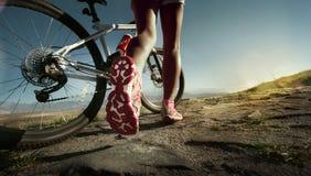 Athletenfrau mit ihrem Fahrrad Lizenzfreie Stockfotografie