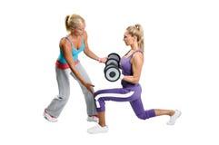 Athletenfrauenübung mit persönlichem Kursleiter Stockbild