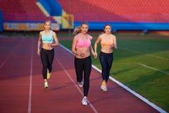 Athletenfrauengruppe, die auf Leichtathletikrennstrecke läuft Stockfotos