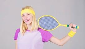 Athletengriff-Tennisschl?ger in der Hand auf grauem Hintergrund Tennissport und -unterhaltung Tennisvereinkonzept M?dchen stockbilder
