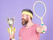 Athletengriff-Tennisschl?ger und goldener Becher Gewinntennisspiel Hippie-Abnutzungssportausstattung des Mannes b?rtige Erfolg un lizenzfreie stockfotografie