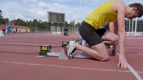 Athletenläufersprinteranfangsstartblock, der am Stadion läuft stock video