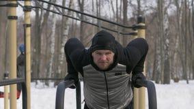 Athletenmann, den Training drückt, ups Übung auf Stange auf WinterSportplatz lizenzfreies stockbild