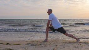 Athletenmann, der Übung zum Bein auf Seeufer, Wasserwellenhintergrund ausdehnend tut stock footage