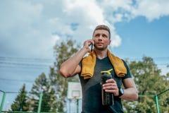Athletenmann steht SommerSportplatzstadt In seiner Handflasche Wasser, stehend nach Übung still Anrufe telefonisch lizenzfreie stockfotos