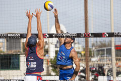Athletenmann-Strandvolleyballspitze und -verteidigung Wand auf dem Netz Arme oben Stockfotografie