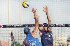 Athletenmann-Strandvolleyballverteidigung Wand auf dem Netz Arme oben Stockbild