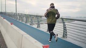 Athletenmannlauftrainings-Lufttraining auf Flussstraße in der ehrfürchtigen Landschaftswelt stock footage