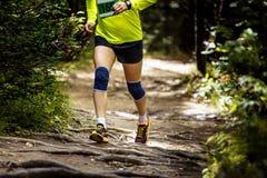 Athletenmarathonläufer, der in Holz läuft Stockfotografie