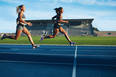 Athletes arrives at finish line on racetrack Royalty Free Stock Photo