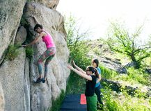 Athletes are bouldering outdoors. A rock climber climbs a rock and his partner insures. Athletes are bouldering outdoors. Group of friends involved in sports in Stock Photography