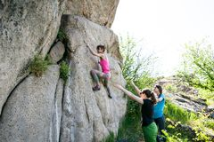 Athletes are bouldering outdoors. A rock climber climbs a rock and his partner insures. Athletes are bouldering outdoors. Group of friends involved in sports in Royalty Free Stock Images