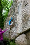 Athletes are bouldering outdoors. Royalty Free Stock Photos