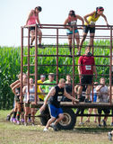 Athletes climb over  obstacles at mudathlon Stock Photos