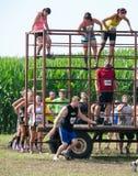 Athletes climb over  obstacles at mudathlon. Athletes climb over obstacles  at  the July 2014 mudathlon in northwest Indiana Stock Photos