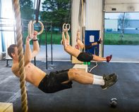 Athletes Dangling On Gymnastic Rings in Box Stock Photo