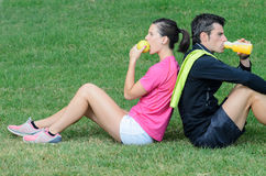 Athletes Diet. Couple of athletes taking a break, eating an apple and drinking isotonic drink Royalty Free Stock Images