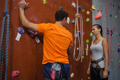 Athletes discussing while standing by climbing wall Royalty Free Stock Photo