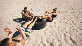 Athletes doing sit-ups on tire. Three young athletes doing abdominal exercise with a truck tire on beach. Athletes doing crossfit workout outdoors Royalty Free Stock Images