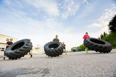 Athletes Doing Tire-Flip Exercise Stock Photo