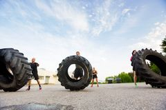 Athletes Doing Tire-Flip Exercise. Group of young athletes doing tire-flip exercise outdoors stock photo