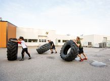 Athletes Doing Tire-Flip Exercise Outdoors Stock Photos