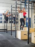 Athletes Exercising On Gymnastic Bars Stock Photo