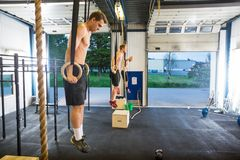 Athletes Exercising On Gymnastic Rings At Stock Image