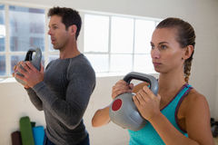 Athletes exercising with kettlebells in gym. Dedicated athletes exercising with kettlebells in gym Royalty Free Stock Image